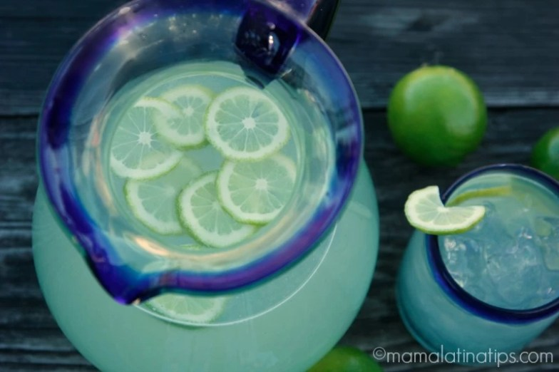 Lime Agua Fresca in a Mexican jar and glass on top of a wooden surface