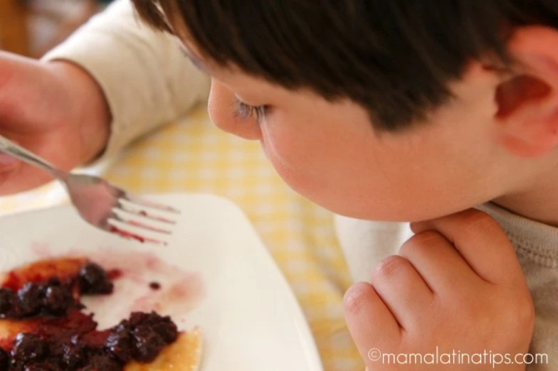 Child eating Lemon Pancakes by mamalatinatips.com