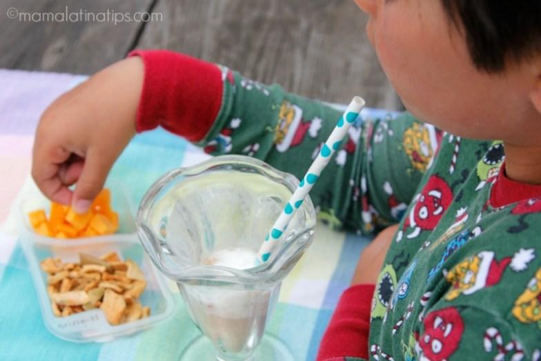 Niño tomando licuado de chocolate y comiendo snacks