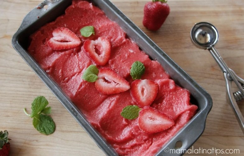 strawberry sorbet in a tray with fresh strawberries on top