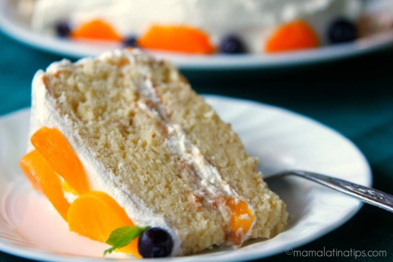 A slice of tres leches cake with peaches