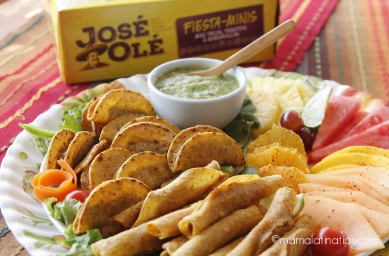 Jose Ole taquitos on a platter with salsa and fruit