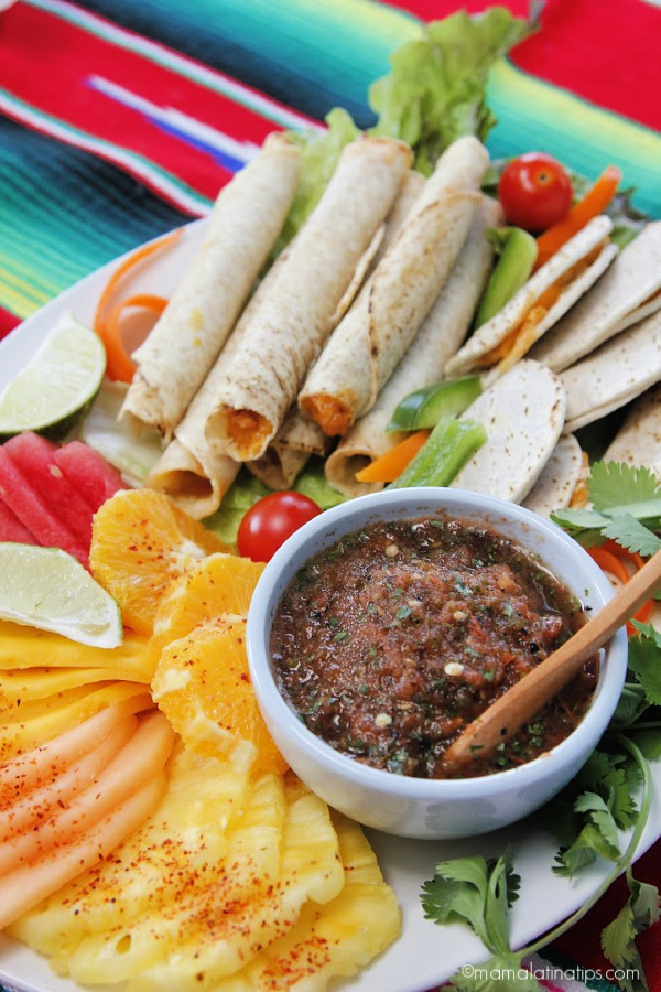 Fruit, taquitos and red salsa on a plater