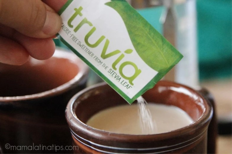 Añadiendo un paquete de endulzante Truvia sobre una taza de café con leche