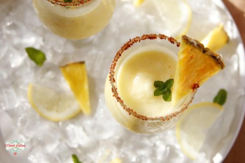 Margarita de piña congelada en un vaso adornado con piña y menta