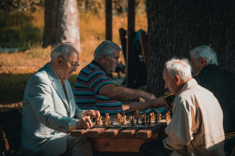 senior citizens playing chess in a wooden table outdoors
