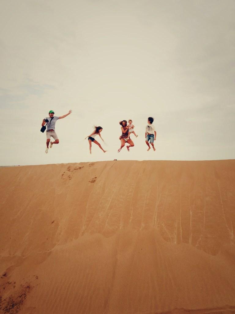 Papá, mamá, dos hijos y un bebé saltando en las dunas