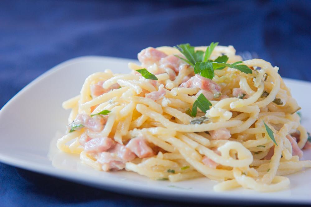 espagueti con jamón, perejil y crema sobre un plato blanco y mantel azul