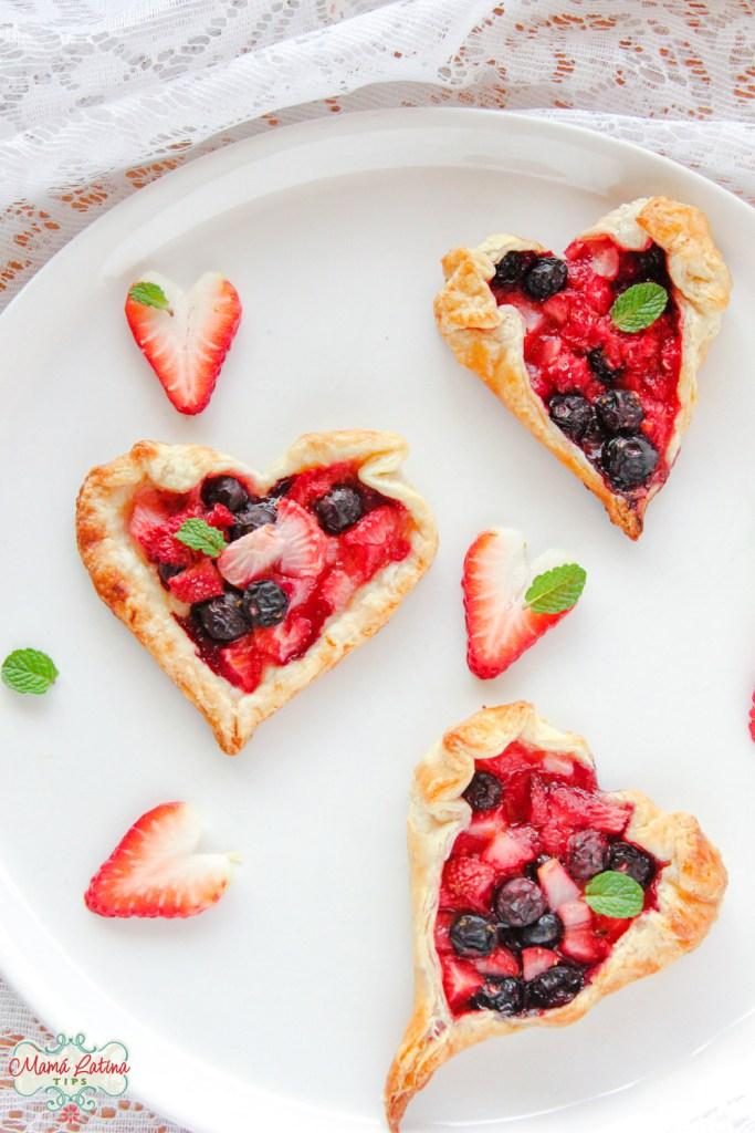 three orange-berry rustic tarts hearth shape on a white platter.