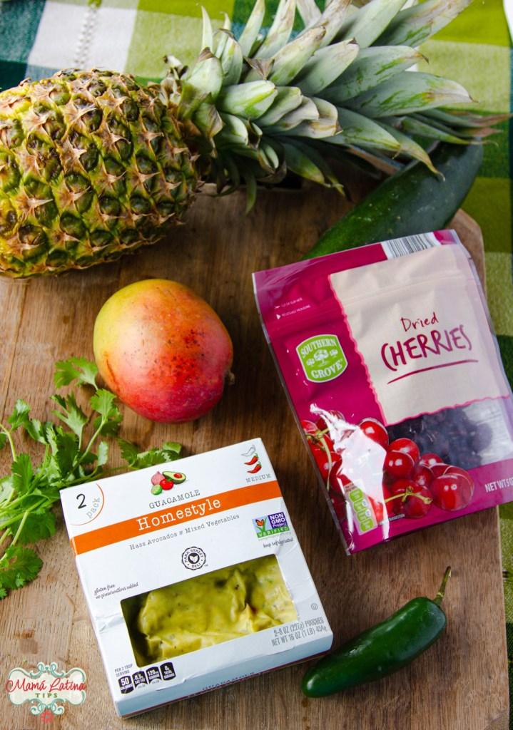 Una piña fresca, mango, pepino, un paquete con una bolsa con guacamole y una bolsa con cerezas secas