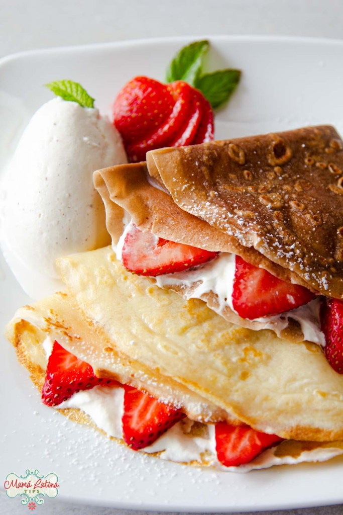 One chocolate crepe and one vanilla crepe with strawberries a la mode
