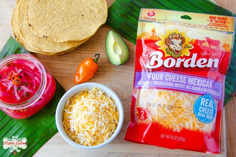 Una bolsa de queso rallado de la marca Borden, tostadas, cebollas moradas en escabeche, un chile habanero y una rebanada de aguacate