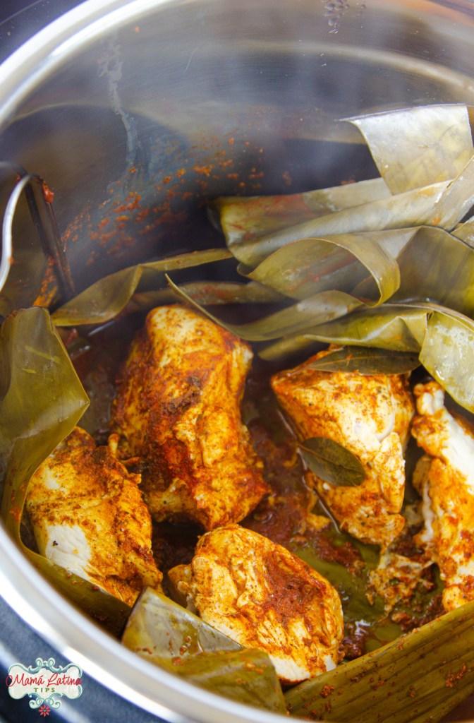 pollo pibil cocido en trozos grande dentro de una olla de presión cubierta de hojas de plátano