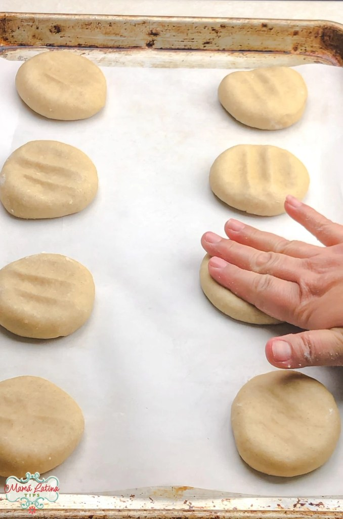 Ocho bollos de pan dulce en una charola para hornear con una mano apachurrándo uno de ellos