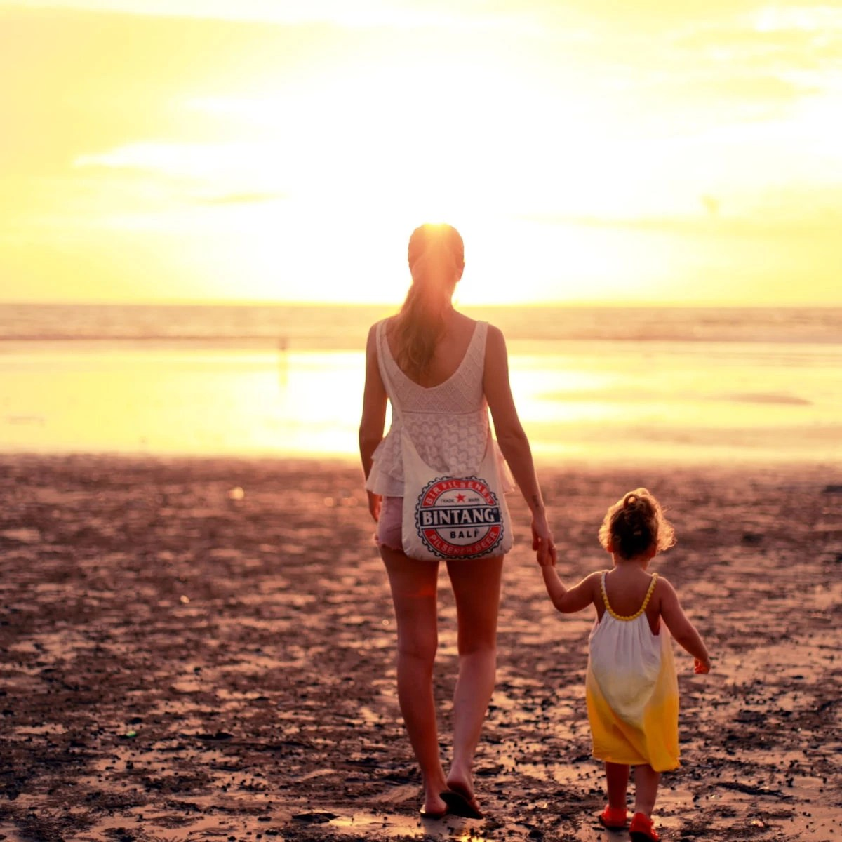 mom and daughter on the beach at sunset