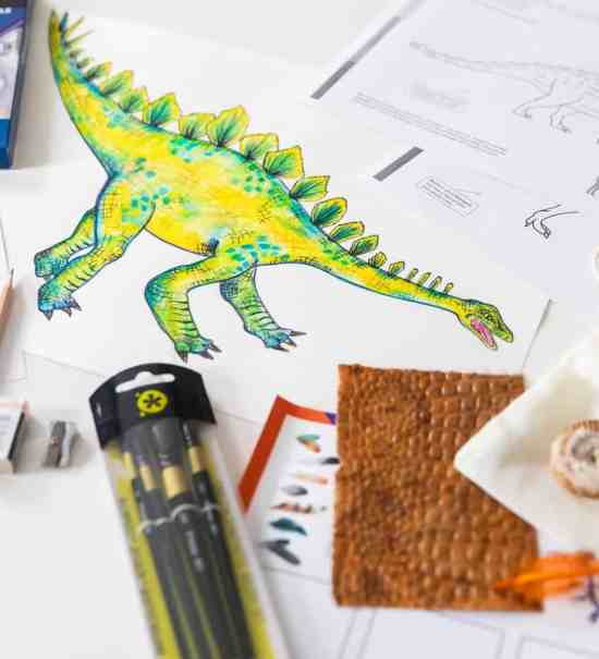 A desk with pencils and a drawing of a stegosaurus