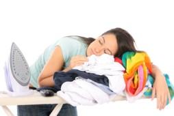 Jeune femme endormie sur une pile de linge à repasser