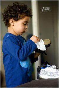 niño lipiando un zapato