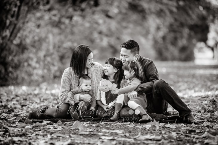 Black and White photograph of family sitting surrounded by fallen leaves