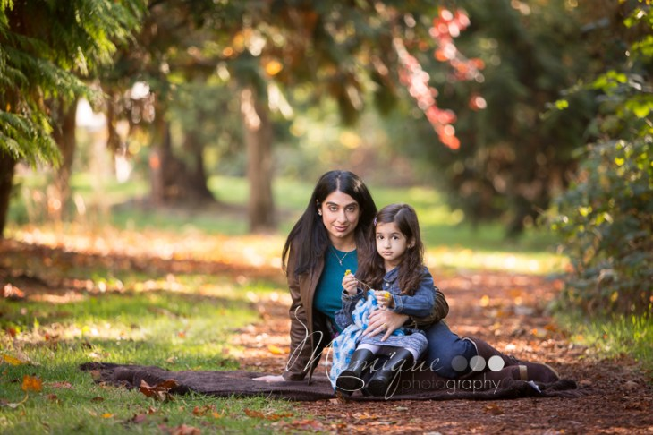 A girl sitting with her mom on a sunny Vancouver fall day portrait