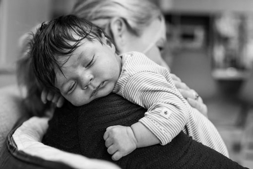 a black and white photo of a newborn baby girl with a full head of hair