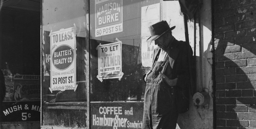 Depression: Unemployed;destitute man leaning against vacant store:photo by Dorothea Lange, circa 1935