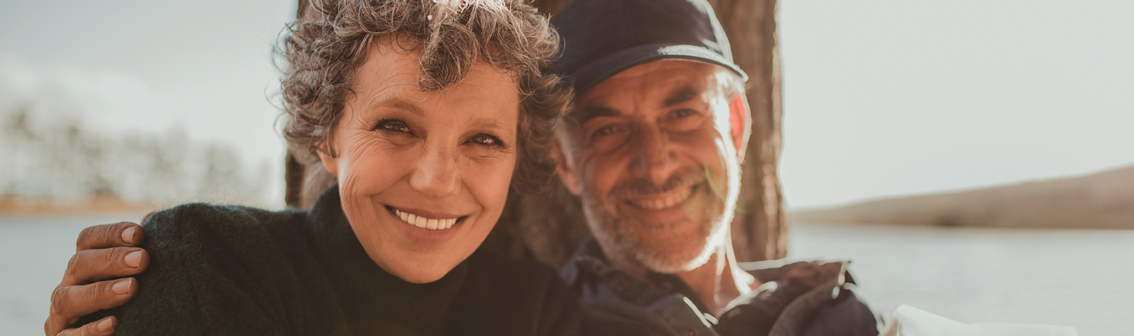 a mature couple smile while they pose for the camera in a bright and sunny scene