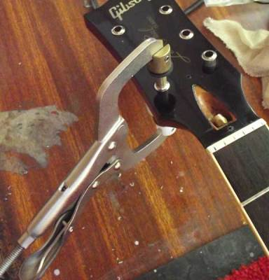 Inserting tuner bushings with a Stewmac bushing press