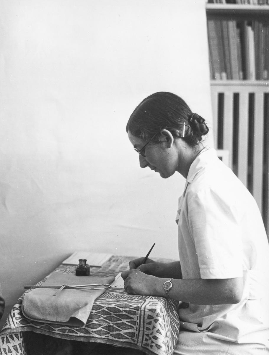 Dans les bureaux de l'Université de Genève, Hélène note scrupuleusement les mesures réalisées sur une patiente et données par son collègue Marc-Rodolphe Sauter (hors champ), août 1940