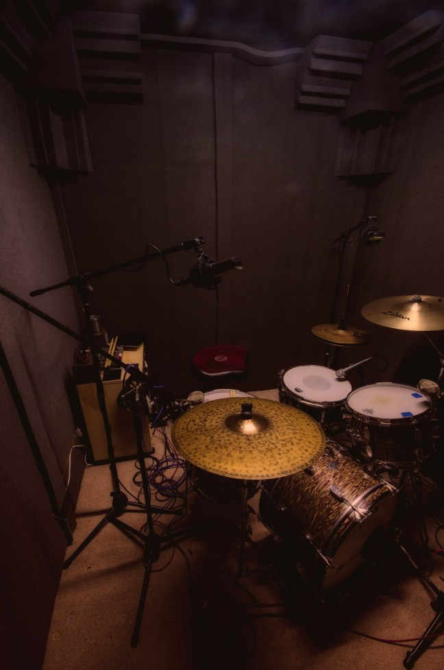 Acoustically-treated sound booth includes corner bass cones for quality of sound