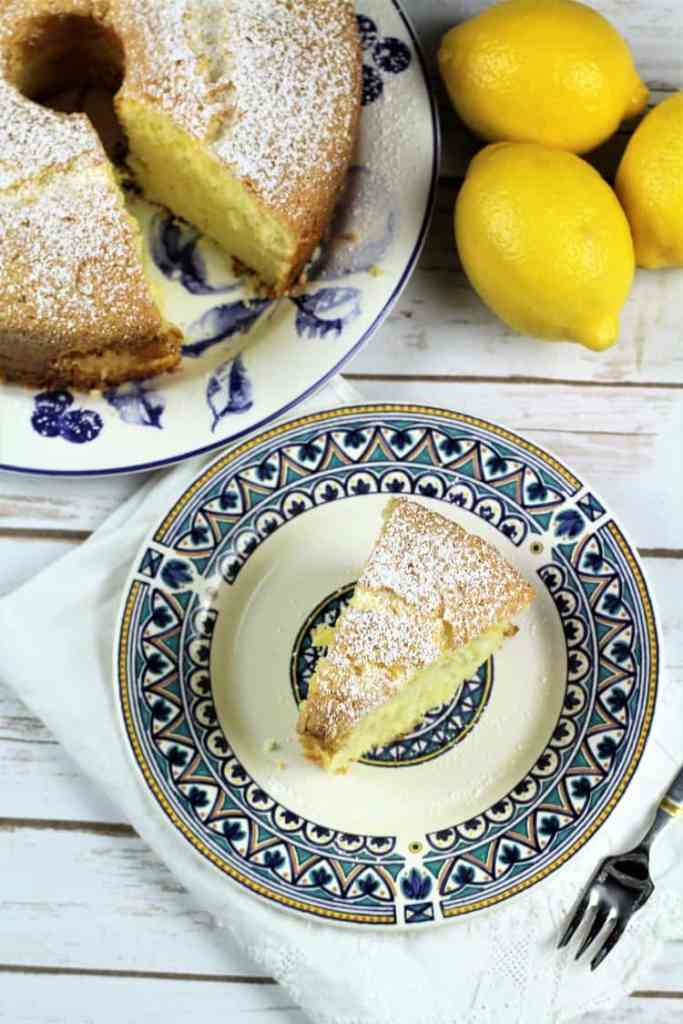 overhead view of slice of Nonna's Sponge Cake with full cake behind it and lemons on the side