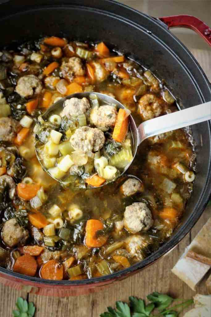 overhead view of meatball and vegetable soup being ladled