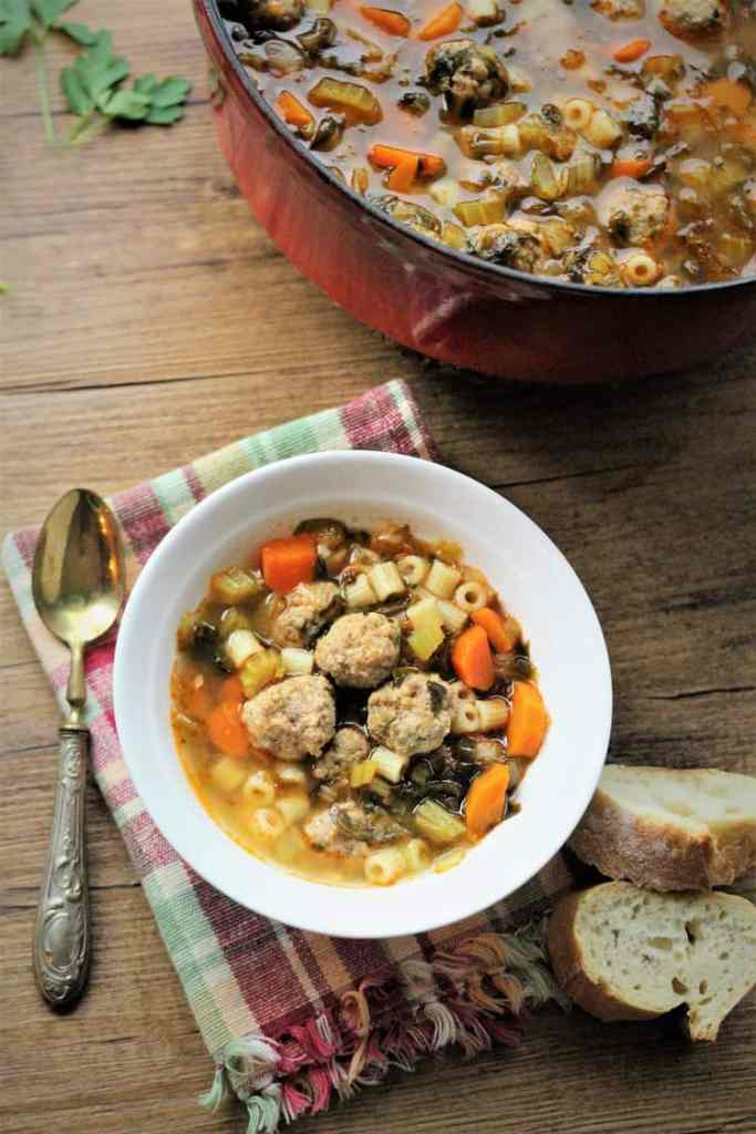 red pot with vegetable and meatball soup with bowl of soup, spoon and sliced bread next to it