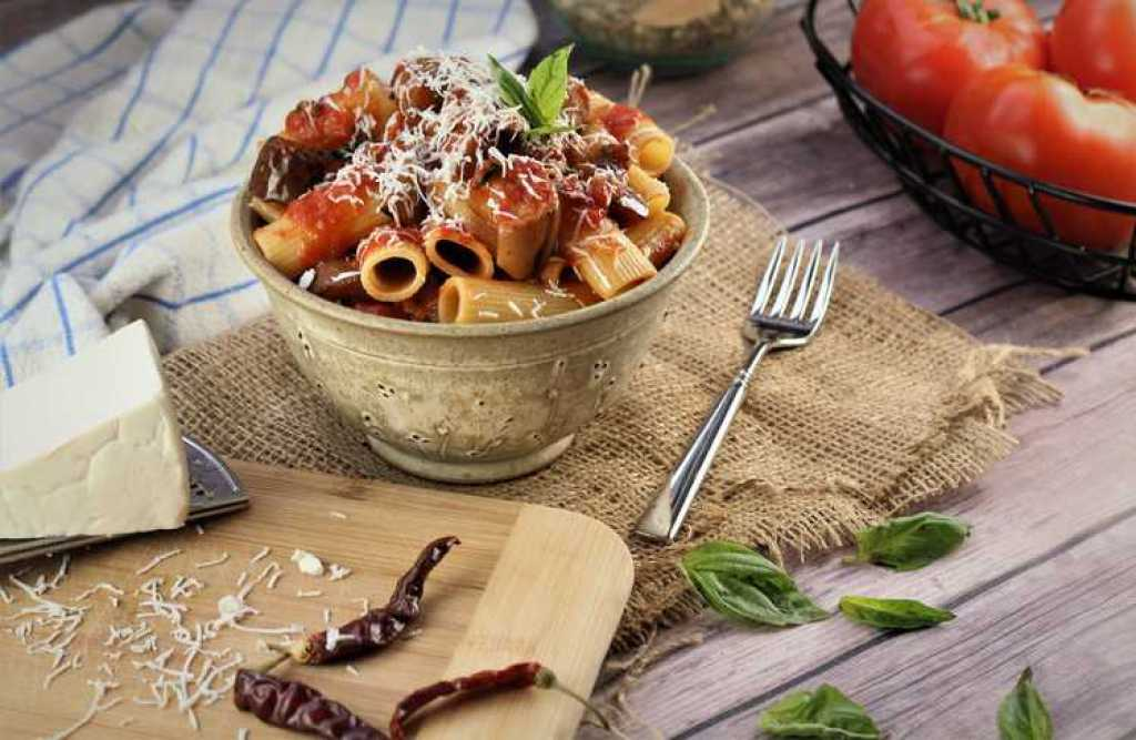 bowl with pasta with eggplant surrounded by hunk of cheese, chili peppers and basket of tomatoes