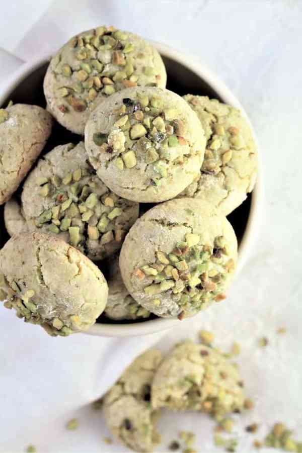 overhead view of cup full of pistachio amaretti with one off to the side on the tablecloth