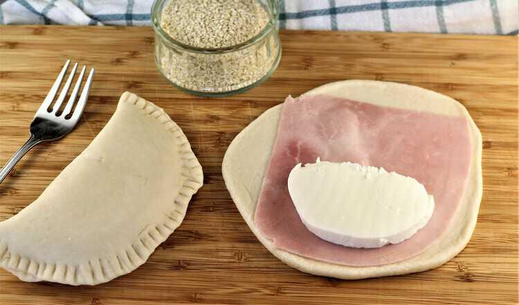 prosciutto cotto and mozzarella on flattened dough to make calzone