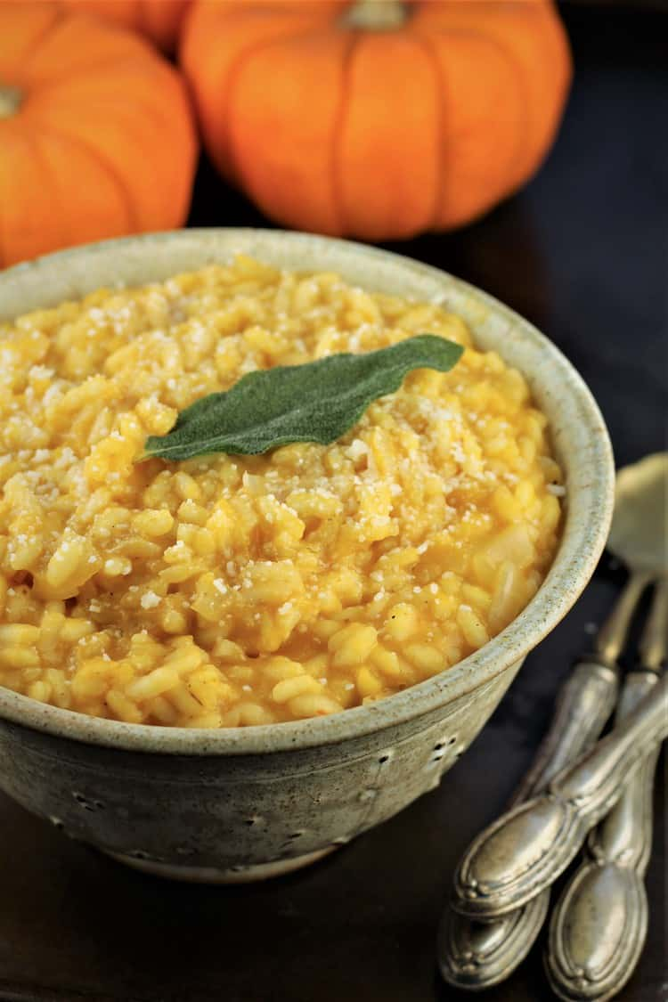 bowl of pumpkin risotto with spoons on the side and pumpkins behind it
