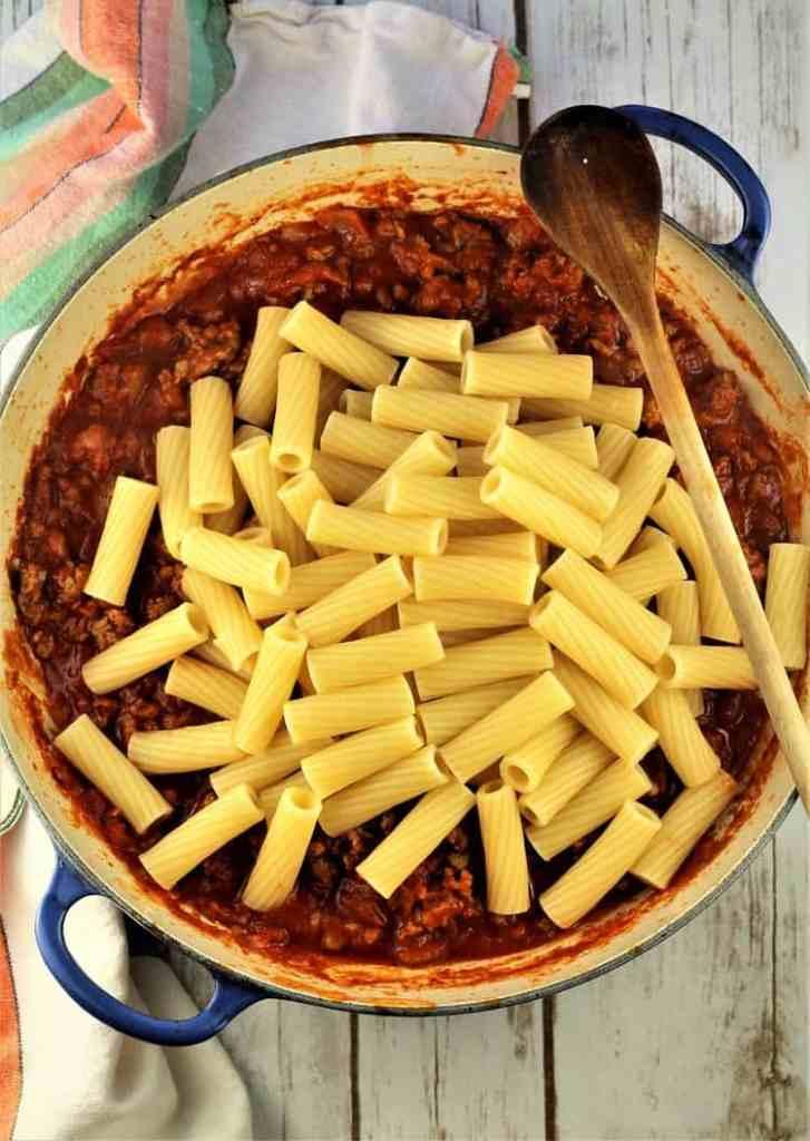 rigatoni pasta over sausage tomato sauce in skillet