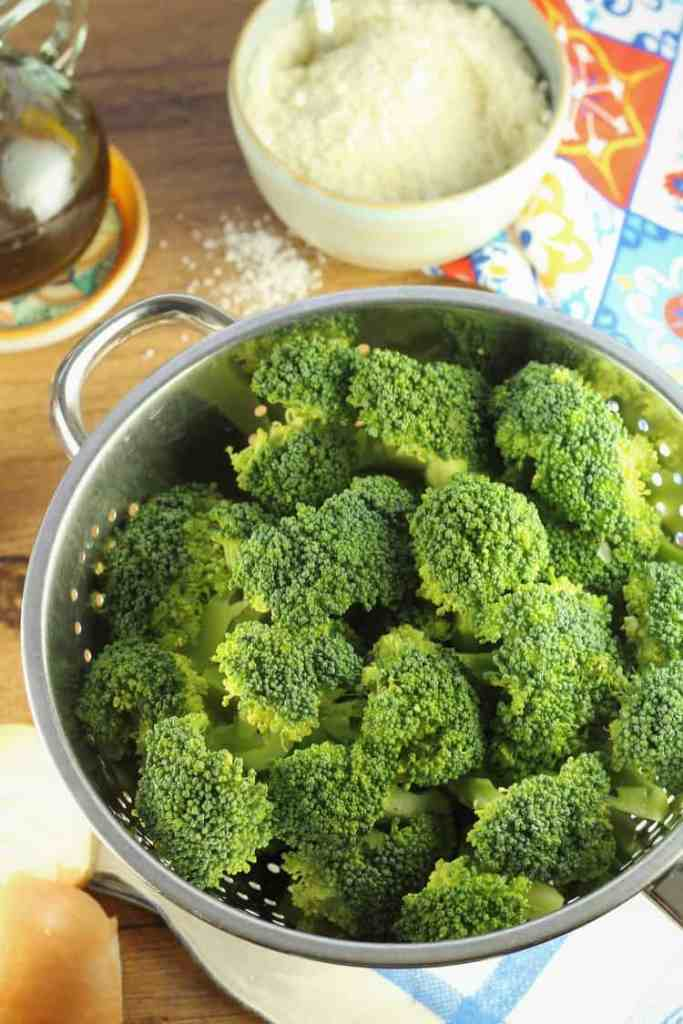 colander filled with broccoli florets, olive oil bottle and cheese bowl in background
