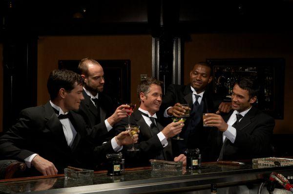 Men in dinner jackets drinking cocktails in bar