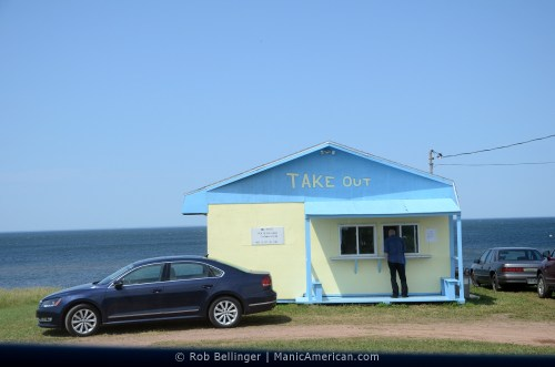 A seaside plywood shack with the words TAKE OUT on it. Several cars surround it. A man is placing an order at the window.