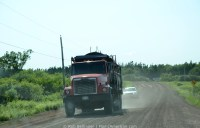 An old dump truck dropping water on a dusty road