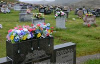 Plastic flowers sit atop tombstones in the rain. Outside Isle aux Morts, Newfoundland.