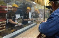 Customers wait for their burgers, while four employees cook them on the other side of a glass divider.