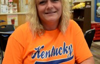 A woman in a shirt that says Kentucky sitting down at a table in a restaurant