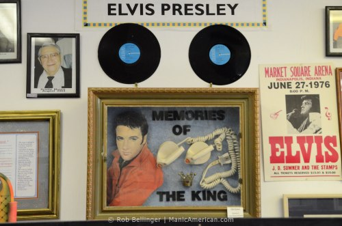 A wall of Elvis Presley memorabilia, such as records and posters, prominently features two defibrillator paddles in a glass case