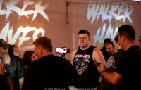 Wrestler Walker Hayes approaches the ring surrounded by fans taking pictures and video. He wears a shirt showing his name in heavy metal font and a wolf surrounded by bloody bones.