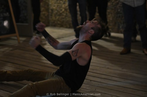 Sam Armstrong, shouting and clenching his fists, falls onto the wooden patio of the venue
