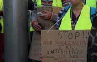 Placard wearing gilets jaunes protestors.