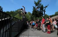 A skater jumps over a fence.